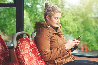 Buy stock photo Cropped shot of an attractive young woman using her cellphone while travelling on the bus