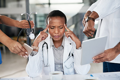 Buy stock photo Shot of a doctor looking stressed out working with demanding colleagues in a hospital