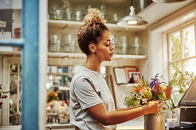 Buy stock photo Cropped shot of an attractive young woman working in her floral boutique