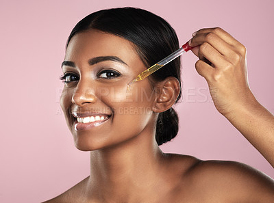Buy stock photo Studio portrait of a beautiful young woman applying essential oil to her face with a dropper posing against a pink background