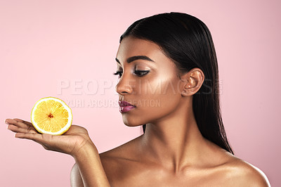 Buy stock photo Studio shot of a beautiful young woman posing with a half an orange against a pink background