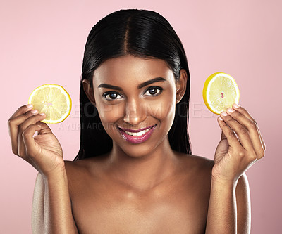Buy stock photo Studio portrait of a beautiful young woman posing with two orange slices against a pink background