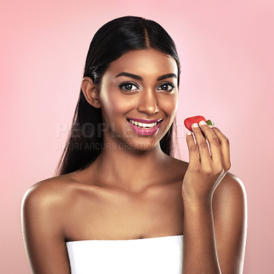 Buy stock photo Studio portrait of a beautiful young woman eating a strawberry while posing against a pink background