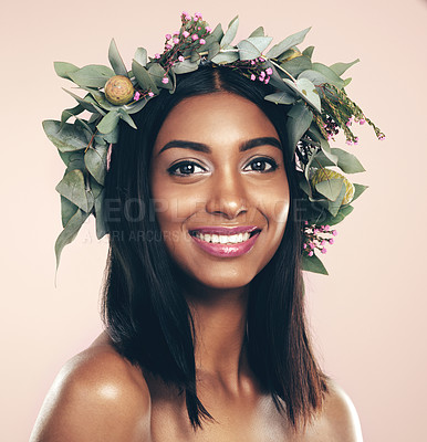 Buy stock photo Studio portrait of a beautiful young woman wearing a wreath while posing against a pink background