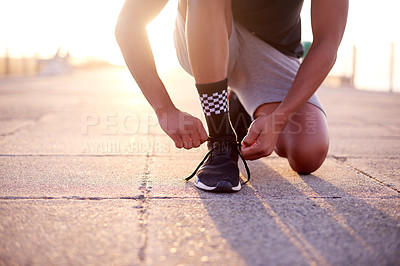 Buy stock photo Shot of an unrecognizable man tying his shoelaces while out for a run