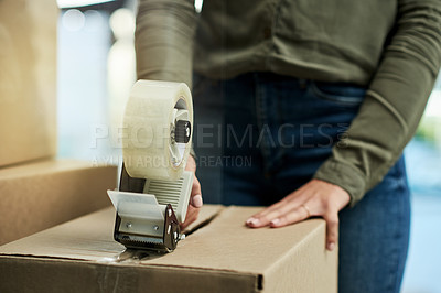 Buy stock photo Cropped shot of an unrecognizable woman packing boxes getting ready to move