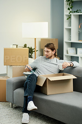 Buy stock photo Shot of a handsome young man reading and drinking coffee while chilling on the sofa in his new home