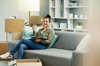 Buy stock photo Cropped shot of a beautiful young woman reading a book and drinking coffee while chilling on the sofa in her new home