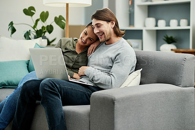 Buy stock photo Cropped shot of a young attractive couple using a laptop together on the sofa in their new home