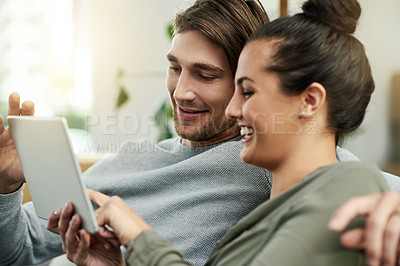 Buy stock photo Cropped shot of a young attractive couple using a tablet in their new home