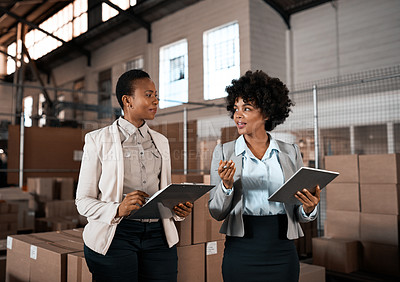Buy stock photo Shot of two factory managers working together in a warehouse