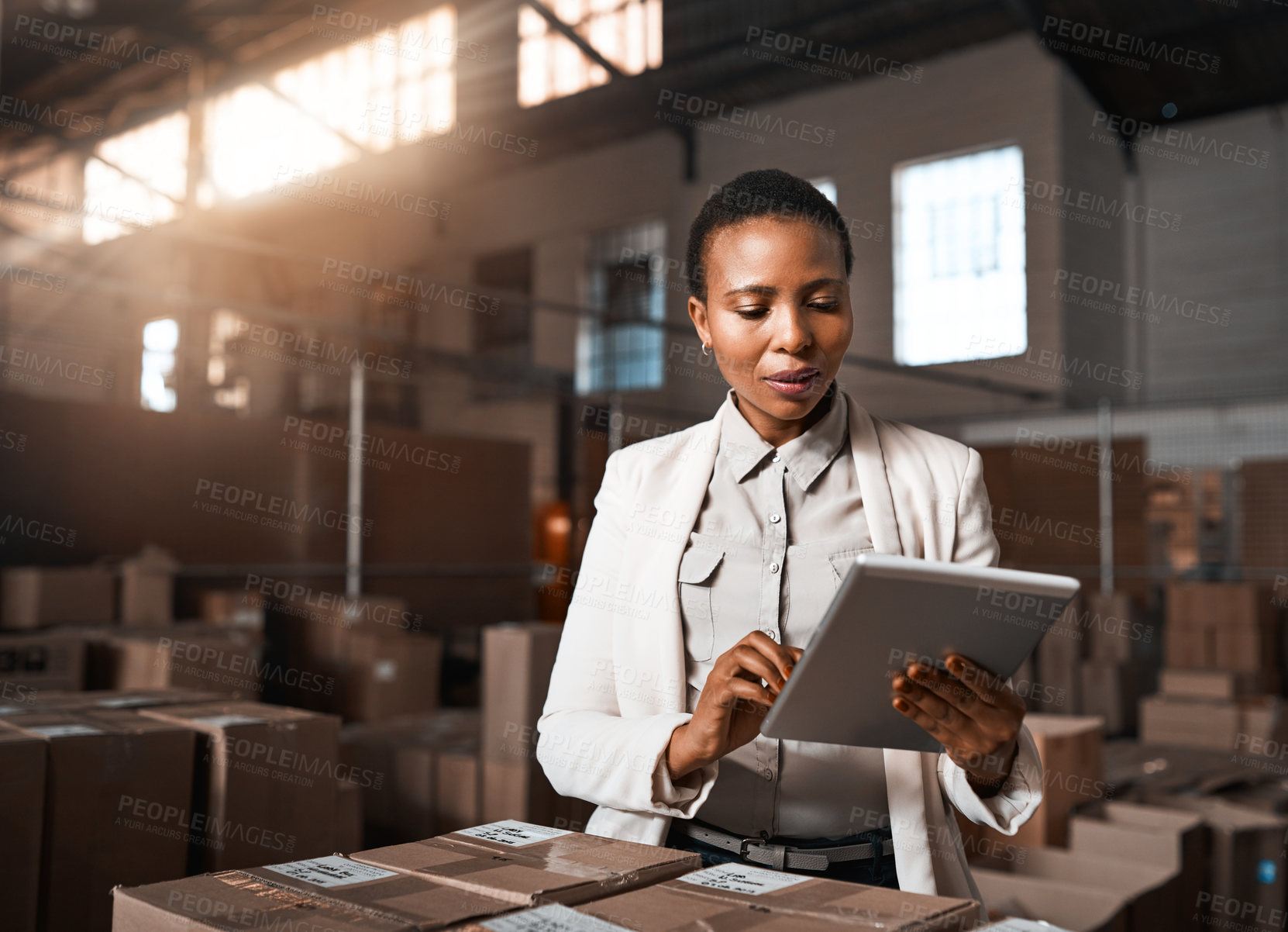 Buy stock photo Shot of a factory manager using a digital tablet in a warehouse