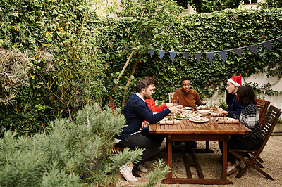 Buy stock photo Shot of a group of young friends having Christmas lunch outdoors