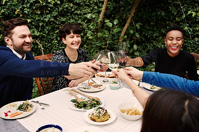 Buy stock photo Cropped shot of a group of friends making a toast while having lunch outside