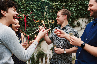 Buy stock photo Shot of a group of friends having fun with sparklers at a party outdoors