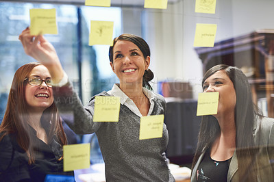 Buy stock photo Cropped shot of a group of businesswomen brainstorming on a glass wall in an office