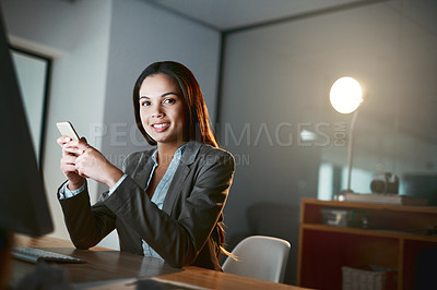 Buy stock photo Portrait of a young businesswoman using a cellphone while working late in an office