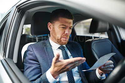 Buy stock photo Cropped shot of a handsome mature businessman looking at his parking ticket while sitting in the driver's seat of his car
