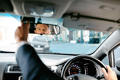 Buy stock photo Cropped shot of a handsome mature businessman adjusting his rearview mirror during his morning commute to work
