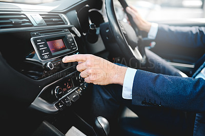 Buy stock photo Cropped shot of an unrecognizable businessman adjusting his car radio while driving himself to work