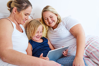Buy stock photo Shot of an adorable little girl using a digital tablet while relaxing in bed with her mother's at home