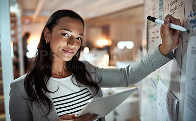 Buy stock photo Cropped portrait of an attractive young businesswoman using a tablet while working on a glass wipe board in her office