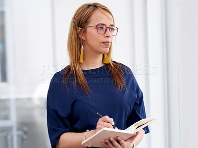 Buy stock photo Shot of a young businesswoman writing in a notebook and looking thoughtful in a modern office