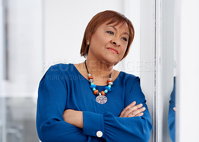 Buy stock photo Shot of a confident mature businesswoman looking thoughtfully out of a window in a modern office