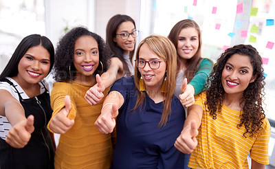 Buy stock photo Portrait of a group of confident businesswomen giving thumbs up together in a modern office