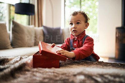 Buy stock photo Shot of an adorable little girl opening her present on Christmas morning