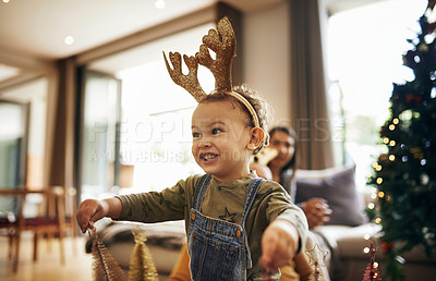 Buy stock photo Cropped shot of an adorable little girl playing with the Christmas decorations at home