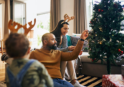 Buy stock photo Cropped shot of a happy young family decorating their Christmas tree for the festive season