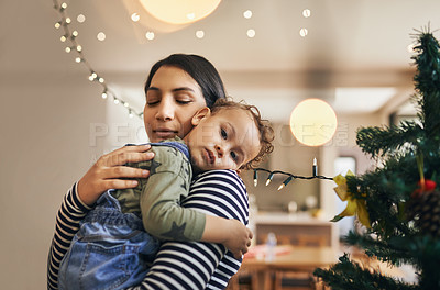 Buy stock photo Cropped shot of an attractive young woman carrying her daughter through the living room on Christmas morning