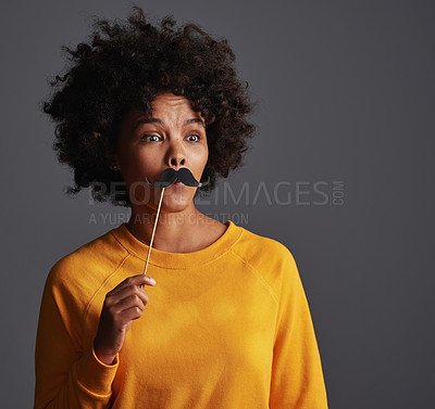 Buy stock photo Shot of a young woman holding up a photo booth prop against a grey background