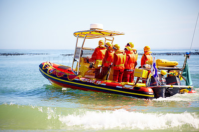 Buy stock photo Full length shot of a group of lifeguards heading out  to sea on a rescue mission