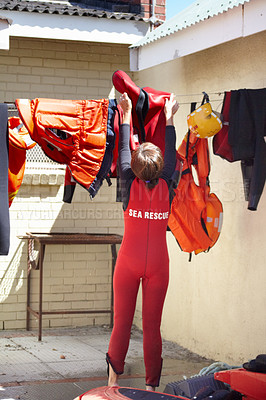 Buy stock photo Rearview shot of an unrecognizable female lifeguard hanging up her uniform after a shift