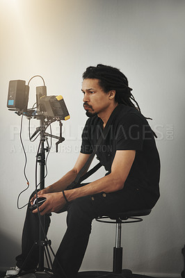 Buy stock photo Behind the scenes shot of a camera operator seated on a chair with camera equipment waiting for the next shot