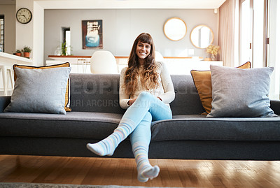 Buy stock photo Portrait of a smiling young woman relaxing on the sofa at home