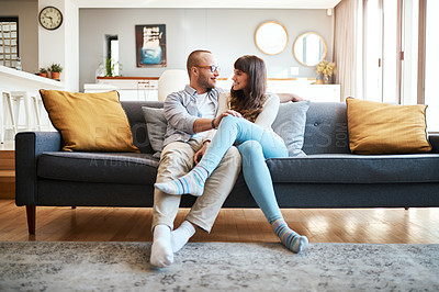 Buy stock photo Shot of a young couple relaxing on the sofa in the living room at home