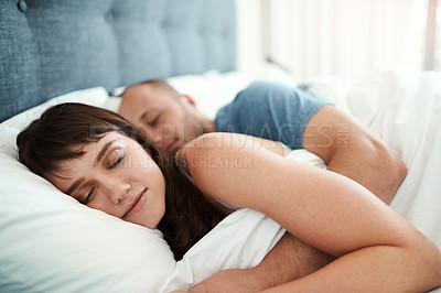 Buy stock photo Cropped shot of a young couple asleep in bed at home