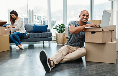 Buy stock photo Portrait of a young man using a laptop while moving house with his wife in the background