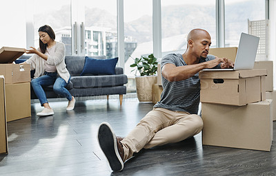 Buy stock photo Shot of a young man using a laptop while moving house with his wife in the background