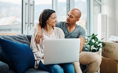 Buy stock photo Shot of a young couple using a laptop while moving house
