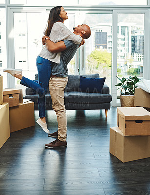 Buy stock photo Shot of a young couple celebrating the move to their new house