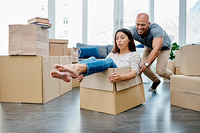 Buy stock photo Shot of a young couple having fun while moving house