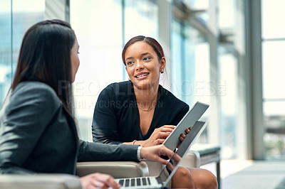 Buy stock photo Shot of two young businesswomen using their wireless devices in the waiting room on a business trip