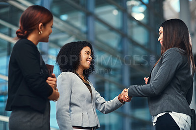 Buy stock photo Shot of confident young businesswomen shaking hands during a discussion in a modern office