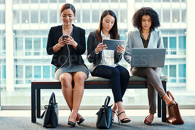 Buy stock photo Shot of a group of young businesswomen using their wireless devices in a waiting room