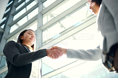 Buy stock photo Low angle shot of two young businesswomen shaking hands in a modern office