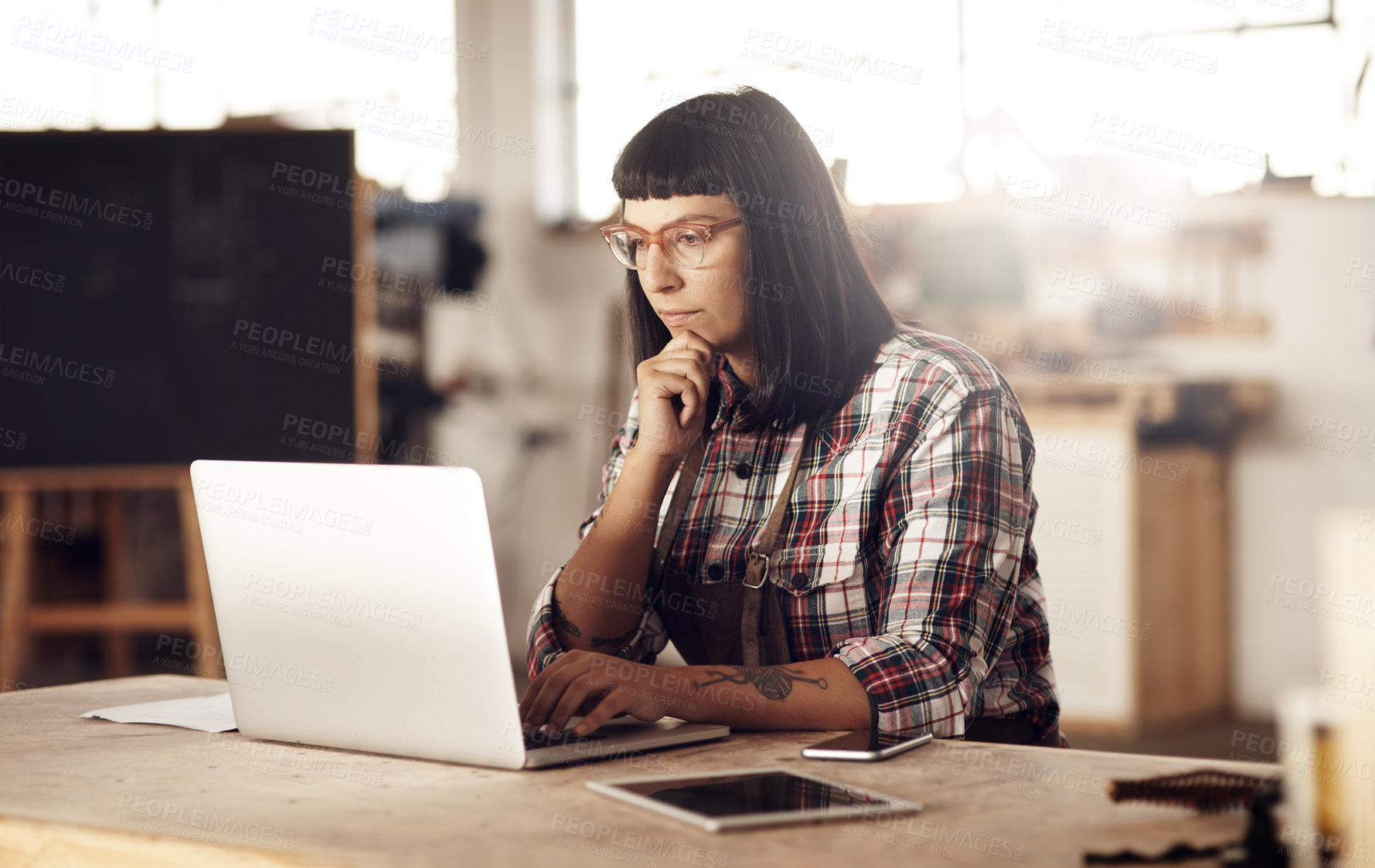 Buy stock photo Cropped shot of an attractive young woman looking thoughtful while working on her laptop in her creative workshop